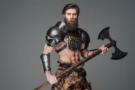 Warlike nordic warrior with and muscular body posing with an axe