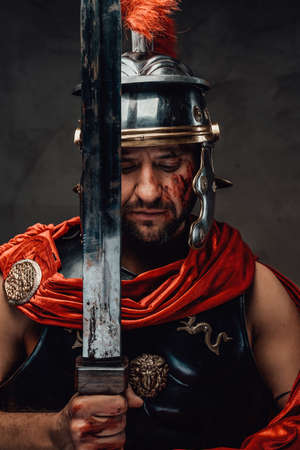 Serious roman warrior posing with sword in dark background