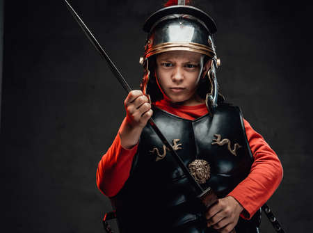 Angry roman boy warrior with sword and red cape Stock Photo