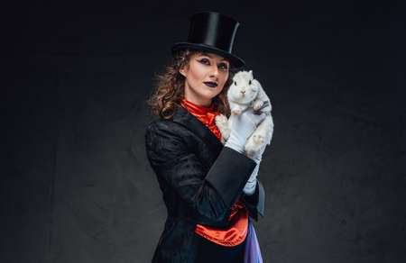 Cheerful conjurer in retro clothes posing in studio with cute rabbit