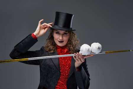 Beautiful woman from circus showing tricks with stick and doves