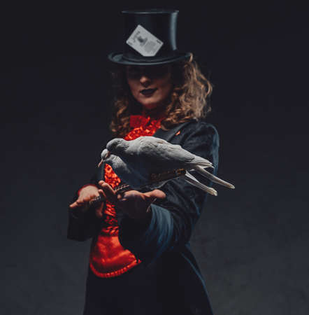 Mystical woman holding a stick with two pigeons in dark background