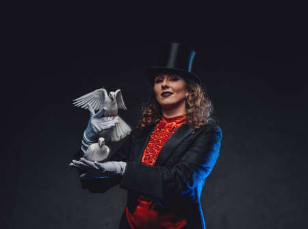 Caucasian female artist dressed in costume with top hat and doves