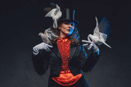 Female artist with curly hairs showing a magic trick with doves