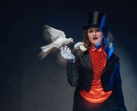 Spectacular female conjurer in dark background with spotlight and doves