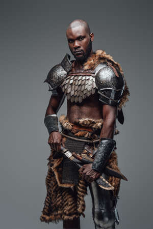 Wild ancient soldier with shaved head and black skin with a blade