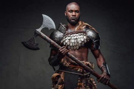 African furious viking in antique armour holding a huge steel axe