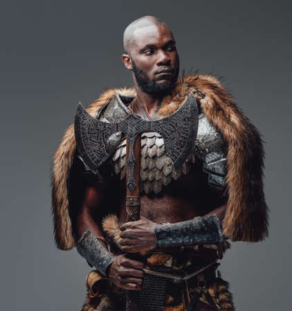Bearded black skinned barbarian with fur and shaved head holding an axe Standard-Bild