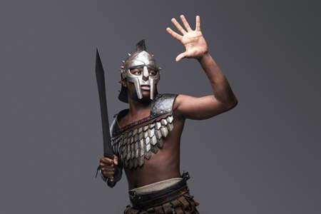Studio shot of african gladiator with sword