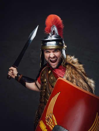 Violent roman soldier screams against dark background Standard-Bild