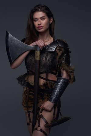 Studio shot of warlike female viking with axe