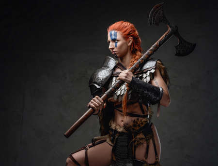 Armoured nordic woman fighter with axe on her shoulder in studio
