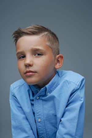 Studio shot of adorable young boy dressed in blue shirt Фото со стока