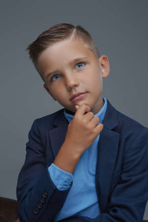 Pensive preteen boy dressed in suit against gray background
