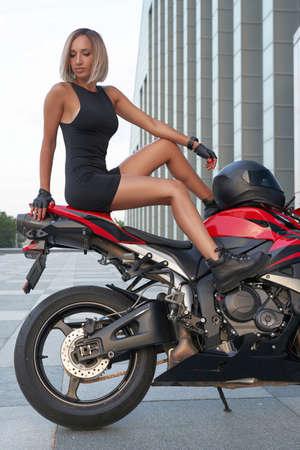 Blond haired sportswoman posing on red bike outside Фото со стока