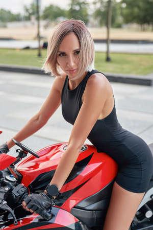 Woman riding custom red bike staring at camera outside Фото со стока