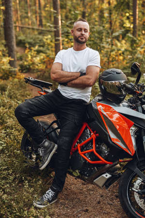 Bearded buy dressed in casual clothing with bike in forest