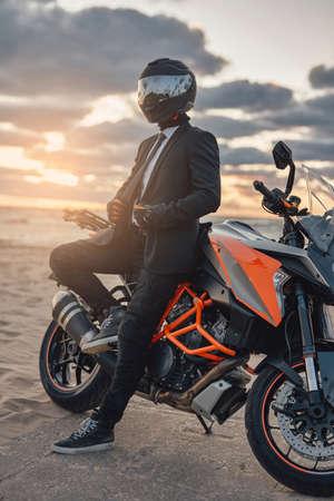 Businessman biker resting on beach with his custom motorcycle