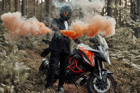Shot of biker dressed in costume with helmet posing with colorful smoke going from his hand in forest.