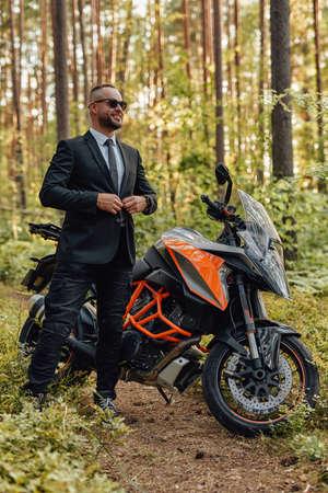 Joyful man in costume with dark motorcycle in woods