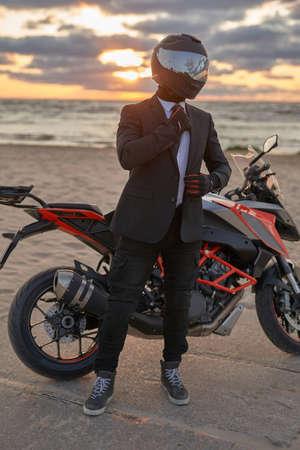 Shot of business man biker posing around dark custom motorcycle on beach against seascape.