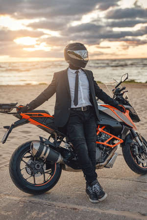 Shot of confident businessperson dressed in suit resting on beach in summertime with motorbike. Фото со стока