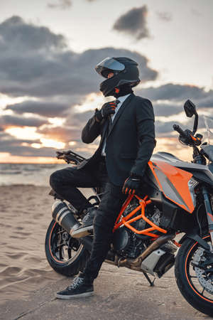 Shot of handsome businessperson weared in suit and helmet relaxing on beach with his modern bike. Фото со стока