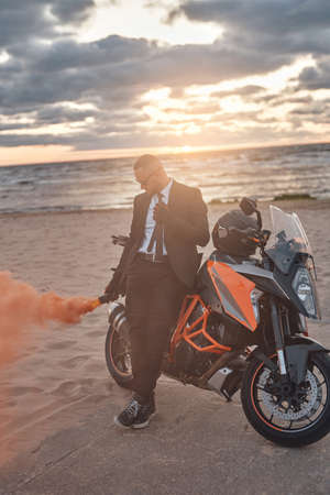 Shot of guy dressed in black suit holding colorful smoke bomb leaning sports bike on beach. Фото со стока
