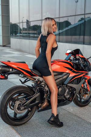 Smiling female biker posing on red custom bike outside Фото со стока