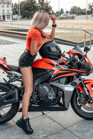 Woman motorcyclist with blond hairs riding motorbike outside