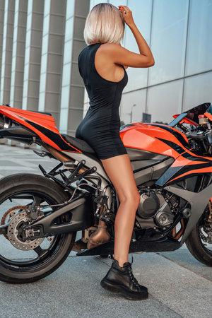 Woman dressed in black sportswear posing on motorbike