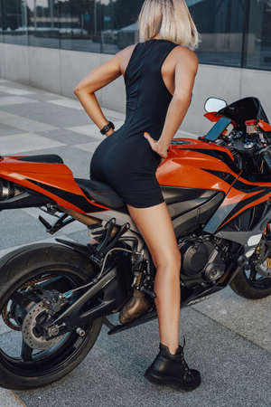 Tanned female biker posing on red custom bike outside