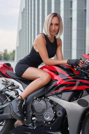 Happy woman riding custom red bike against city building Фото со стока