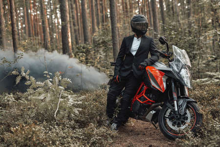 Cool biker in suit posing with bike against forest with smoke Фото со стока