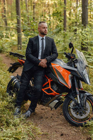 Handsome man in costume with dark motorcycle in woods