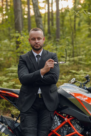 Cool man and black red colored motorbike in forest