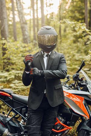 Handsome biker with helmet and dark motorcycle in forest