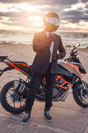 Active businessman with modern sports motorbike on beach