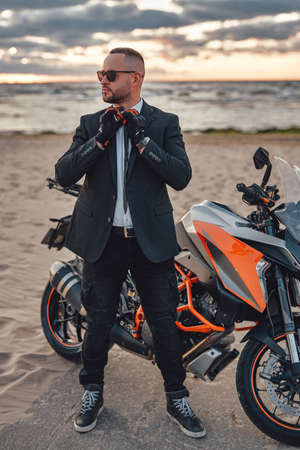 Cool guy with sunglasses and dark motorcycle on beach Фото со стока