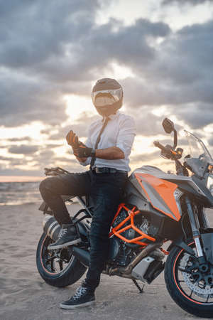 Confident biker in white shirt and helmet with motorbike