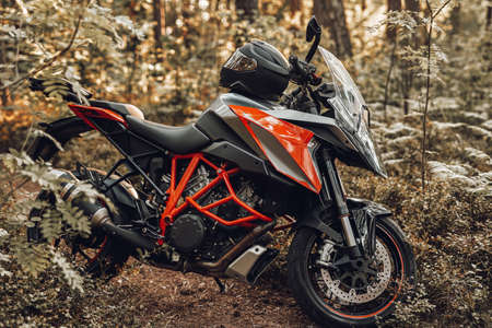 Modern black red colored motorcycle with helmet in forest