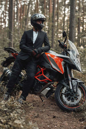 Man weared in black suit with dark motorcycle in forest