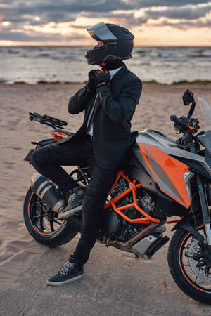 Cool businessman with motorcycle helmet posing against seascape
