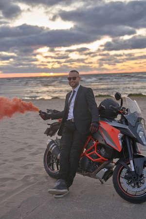 Stylish man with smoke bomb and motorbike on beach