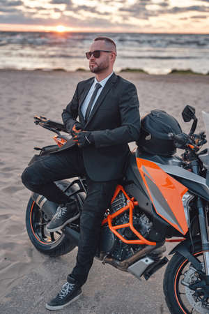 Male biker relaxing on beach with his sports motorbike