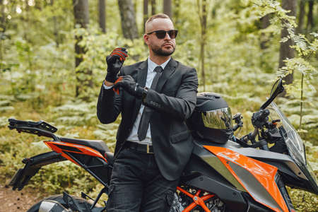 Businessman wearing protective gloves posing in summer forest