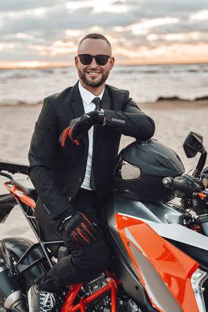 Joyful motorcyclist in suit riding sports bike on beach