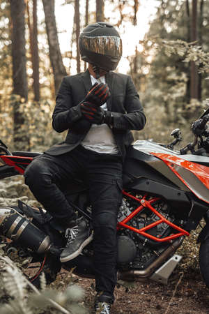 Businessman biker with gloves and helmet posing in forest