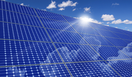 large solar panels under the blue sky with lively clouds, reflecting the sun