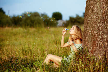 blowing bubbles: young blond woman blowing soap bubbles